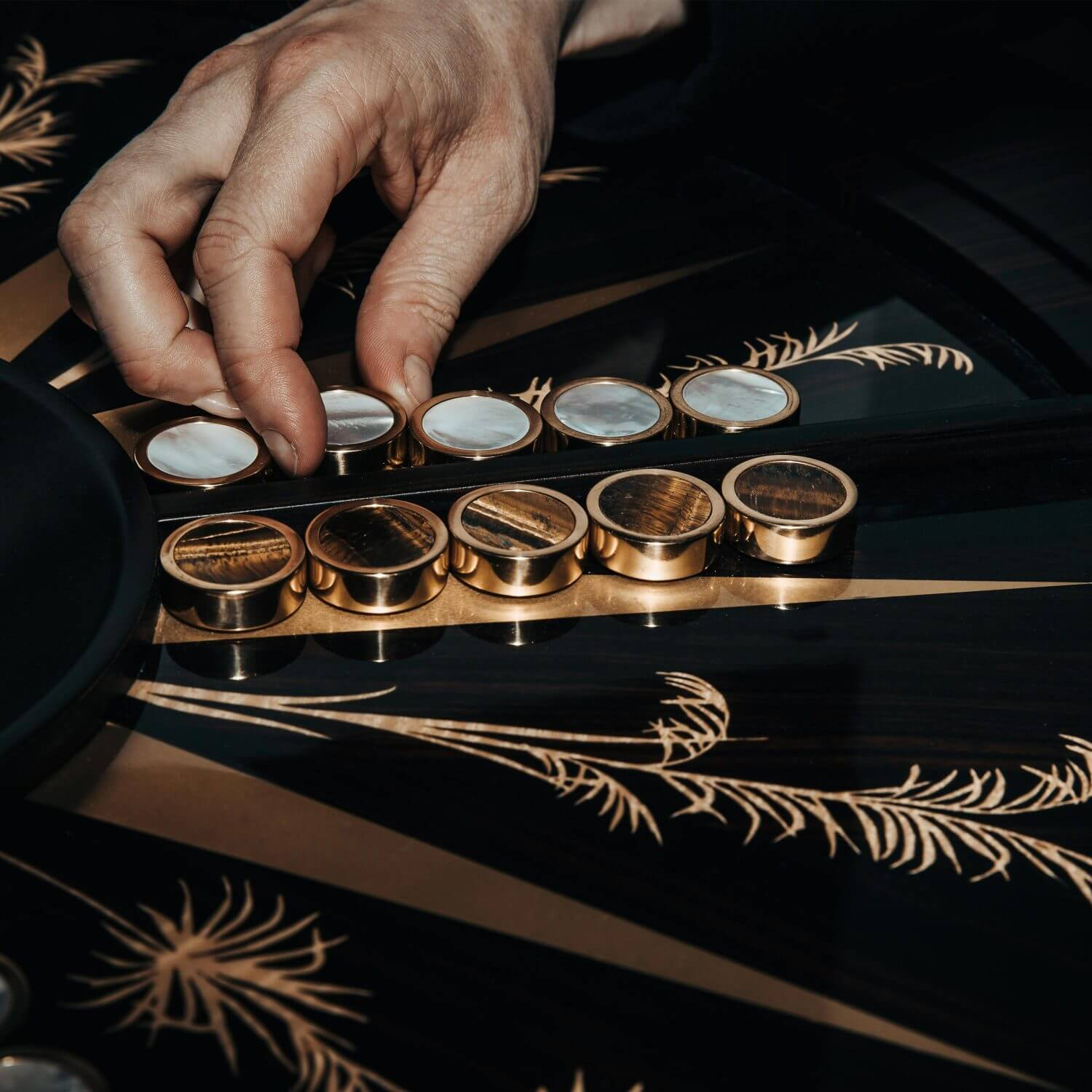 A man playing backgammon on a custom games table